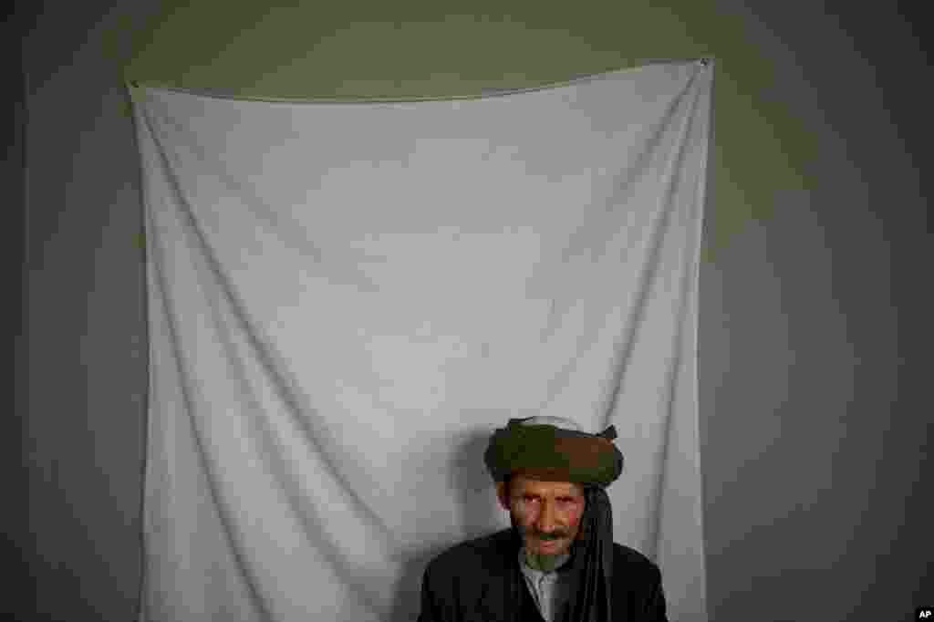 A man waits to have his picture taken for his registration card on the last day of voter registration for the upcoming presidential elections outside a school in Kabul, April 1, 2014.