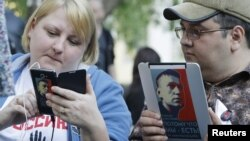 Opposition activists use electronic devices pictured with portraits of prominent anti-corruption blogger Alexei Navalny during a four day-long protest in a boulevard in central Moscow, May 10, 2012.