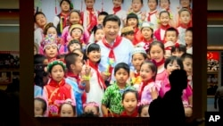 FILE - A visitor walks past a photo, Sept. 28, 2017, of Chinese President Xi Jinping surrounded by children at an exhibition highlighting five years of progress under Xi's leadership in Beijing. The birthrate in China fell in 2017 despite the easing of fa