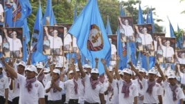 Supporters of the ruling Cambodian Peoples Party (CPP) march with party flags, posters