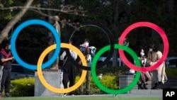 Orang-orang mengambil gambar cincin Olimpiade yang dipasang oleh Museum Olimpiade Jepang di Tokyo pada hari Jumat, 19 Maret 2021. (Foto: AP/Hiro Komae)