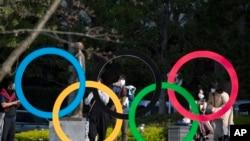 Orang-orang mengambil gambar logi Olimpiade yang dipasang oleh Museum Olimpiade Jepang di Tokyo pada hari Jumat, 19 Maret 2021. (Foto: AP/Hiro Komae)