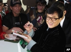 FILE - Martial arts star Jackie Chan says he's ashamed of his son, indicted on a drug charge. Here, the elder Chan signs autographs in Seoul, South Korea, Jan. 19, 2014.