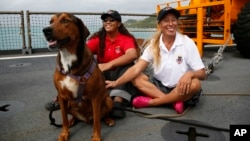 Jennifer Appel, right, and Tasha Fuiava sit with their dogs on the deck of the USS Ashland, Oct. 30, 2017, at White Beach Naval Facility in Okinawa, Japan.