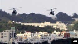 FILE - US military helicopters flying over the US Marine Corps Futenma Air Base in Ginowan, Okinawa Prefecture, Japan.