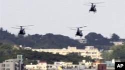 FILE - US military helicopters flying over the US Marine Corps Futenma Air Base in Ginowan, Okinawa Prefecture, Japan. The Navy has seen increased pressure in Okinawa where residents are calling for the removal of U.S. bases