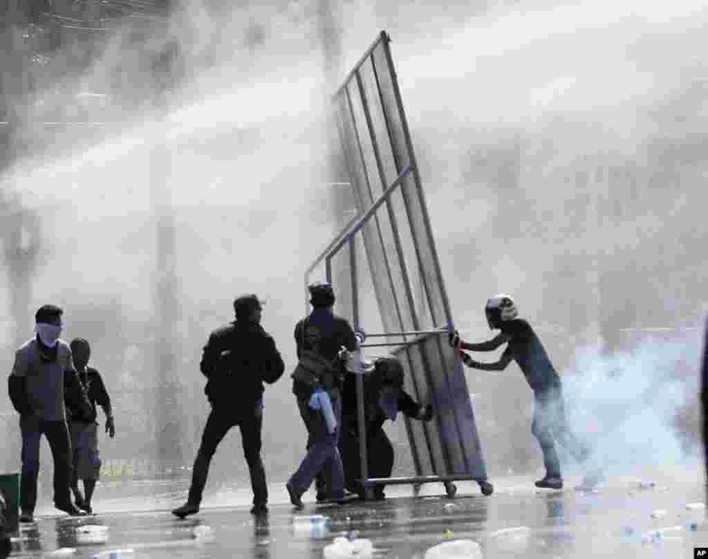 Anti-government protesters use self-made barricade against the water cannons and tear gas fired by riot police in Bangkok.