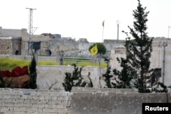 FILE - A Hezbollah flag flutters in a government-controlled area, as seen from the rebel-controlled area of Karm al-Tarab frontline, near Aleppo international airport April 22, 2015.