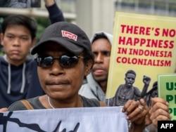 Ilustrasi. Para aktivis membawa poster-poster saat berdemo untuk menarik perhatian kepada isu HAM Papua, di depan Kedutaan Besar Belanda di Jakarta, di tengah kunjungan Raja Belanda Willem-Alexander, 12 Maret 2020. (Foto: AFP)