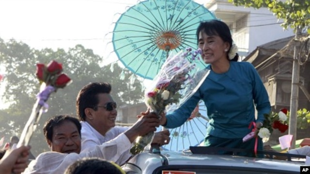 Pro-democracy leader Aung San Suu Kyi receives flowers from supporters on her vehicle during her election campaign trip to Thone-Gwa township in Rangoon, Burma, February 26, 2012.