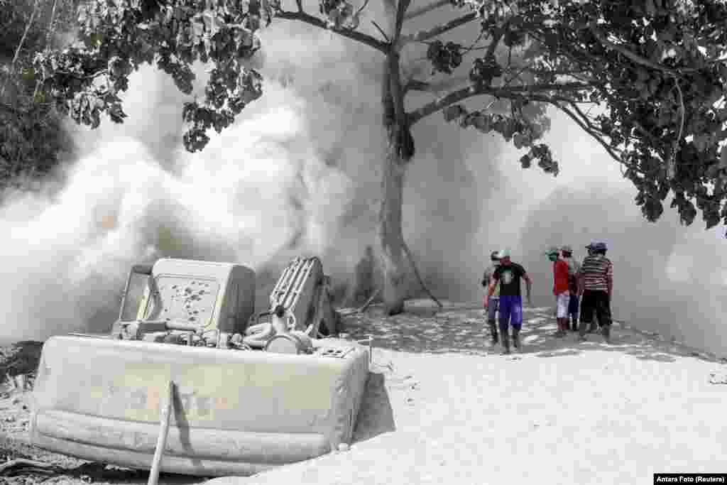 People are seen on a road blanketed with volcanic ash from the erupting Mount Semeru in Lumajang, East Java Province, Indonesia.