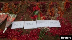 Flowers and notes are pictured on the ground at the entrance of the Army Public School, which was attacked by Taliban gunmen, in Peshawar, Dec. 22, 2014.