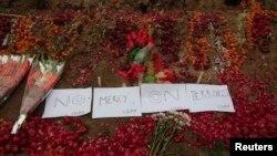 在白沙瓦遇袭的陆军公共学校的地上有鲜花和标语:绝不宽恕恐怖分子