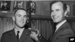 George W. Bush, left, is shown with his father, George H.W. Bush in this photo from 1968.