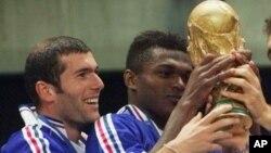 Zinedine Zidane, à gauche, tient le trophée avec Marcel Desailly lors de Coupe du monde de football remportée avec l'équipe de la France 3-0 contre le Brésil le 12 juillet 1998.
