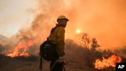Seorang petugas pemadam kebakaran di menyaksikan api dekat Jalan Placenta Caynon Road di Santa Clarita, California (24/7). (AP/Ringo H.W. Chiu)