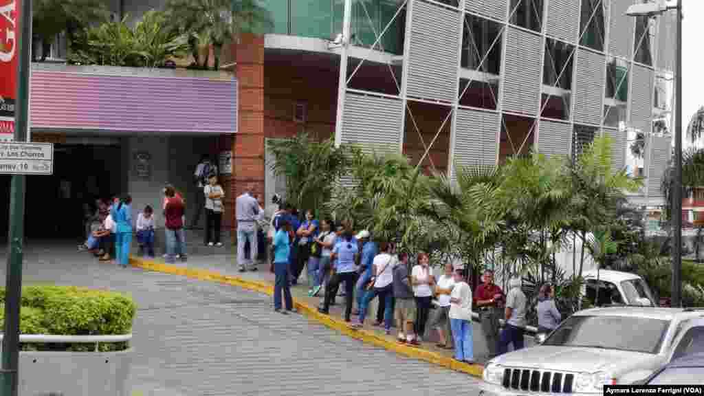 Desde muy temprano los caraqueños hacen fila frente a los supermercados a la espera de poder comprar los alimentos.