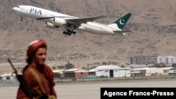 FILE - A Taliban fighter stands guard as a Pakistan International Airlines plane, the first commercial international flight to land since the Taliban retook power, takes off at the airport in Kabul on Sept. 13, 2021.