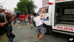 Para demonstran memukul mobil van polisi Filipina setelah menabrak kerumunan demonstran di Manila, Rabu (19/10).