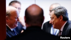 Ireland's Finance Minister Michael Noonan talks to European Central Bank (ECB) President Mario Draghi (R) during an eurozone finance ministers meeting in Brussels, Dec. 9, 2013.