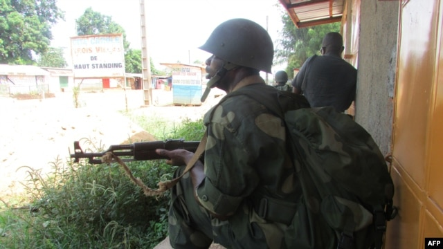 FILE - African Union intervention force secures the area during an operation to free the way leading to the north of Bangui, March 25, 2014.