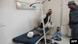 Một người đàn ông và bé trai bị thương trong vụ đánh bom tự sát ngồi trong bệnh viện chính ở thành phố Khost, ngày 1/10/2012