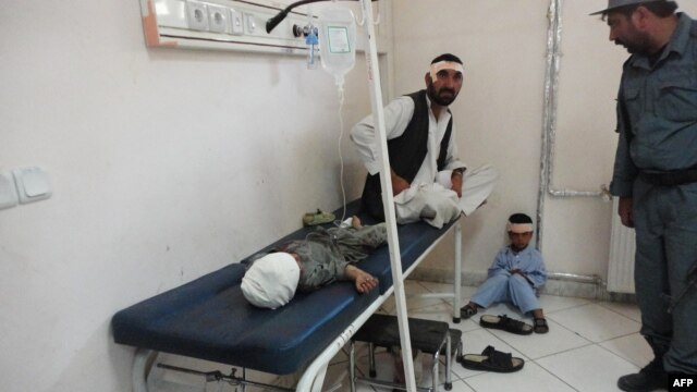 An Afghan policeman looks at a wounded man and children sitting in the main hospital in Khost city on October 1, 2012.