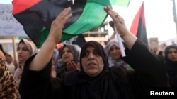 FILE - Women take part in a demonstration against the country's parliament and in support of the coalition of fighters called the Benghazi Revolutionaries Shura Council, at Freedom Square, Benghazi, Aug. 29, 2014.