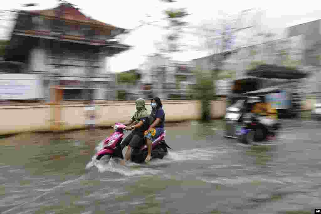Residents wear masks to prevent the spread of the coronavirus ride motorcycles as they negotiate a flooded road due to Typhoon Molave in Pampanga province, northern Philippines.