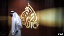 FILE- In this Wednesday Nov. 1, 2006, file photo, a Qatari employee of Al-Jazeera Arabic language TV news channel walks past the logo of Al-Jazeera in Doha, Qatar.