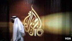 Tư liệu - Một nhân viên người Qatar của kênh tin tức Al-Jazeera tiếng Ả-rập đi ngang qua logo của Al-Jazeera ở Doha, Qatar.