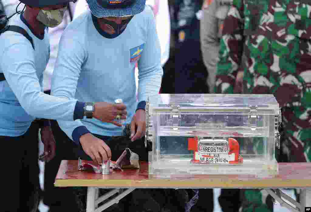 Indonesian Navy personnel handle a box containing the flight data recorder recovered from the crash site of the Sriwijaya Air flight SJ-182 in the Java Sea at Tanjung Priok Port.