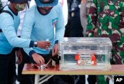 Personel TNI AL memegang kotak berisi perekam data penerbangan yang ditemukan dari lokasi jatuhnya penerbangan Sriwijaya Air SJ-182 di Laut Jawa di Pelabuhan Tanjung Priok. (Foto: AP)