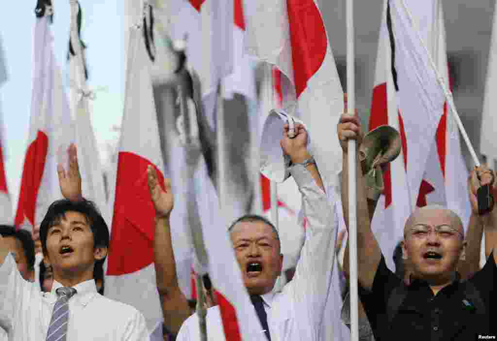 "Members of the nationalist movement ""Ganbare Nippon"" hold Japanese national flags raise as they shout ""banzai"" after a march to pay tribute to the war dead at Yasukuni Shrine in Tokyo, August 15, 2013."