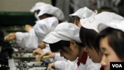 Para pekerja sedang bekerja di komplek Foxconn di Shenzhen, Tiongkok Selatan.