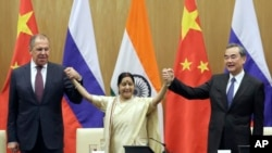 Indian Foreign Minister Sushma Swaraj, center, holds hands with her Chinese and Russian counterparts Wang Yi, right and Sergey Lavrov after a press statement at the end of their meeting in New Delhi, India, Monday, Dec. 11, 2017.