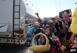 Seorang perempuan menaburkan mawar saat orang-orang berkumpul untuk menyambut kapal tanker yang membawa bahan bakar dari Suriah tiba di kota Baalbeck, di lembah Bekaa, Lebanon, 16 September 2021.