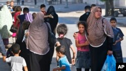 Phụ nữ và trẻ em Palestine rời bỏ nhà cửa chạy lánh nạn ở thành phố Gaza, ngày 16/7/2014.