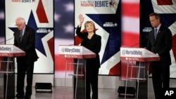 Hillary Clinton waves as Bernie Sanders, left, and Martin O'Malley prepare before a Democratic presidential primary debate, Nov. 14, 2015, in Des Moines, Iowa.
