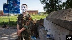 우크라이나 동부 카르키프시 외곽의 한 고속도로에서 얼굴을 가린 친러 분리주의 반군이 도로를 차단한채 불법 검문 활동을 벌이고 있다.