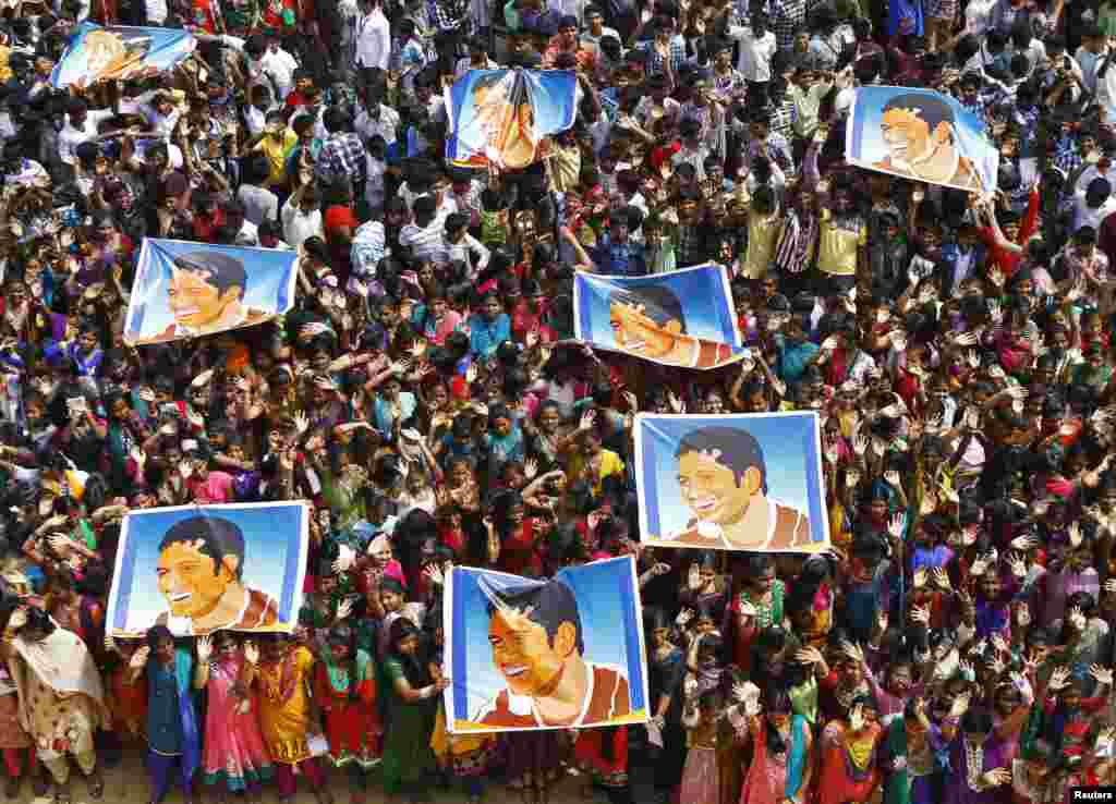 School children wave as they hold posters of Indian cricketer Sachin Tendulkar at an event to honor him inside a school, Chennai, India, Nov. 14, 2013.