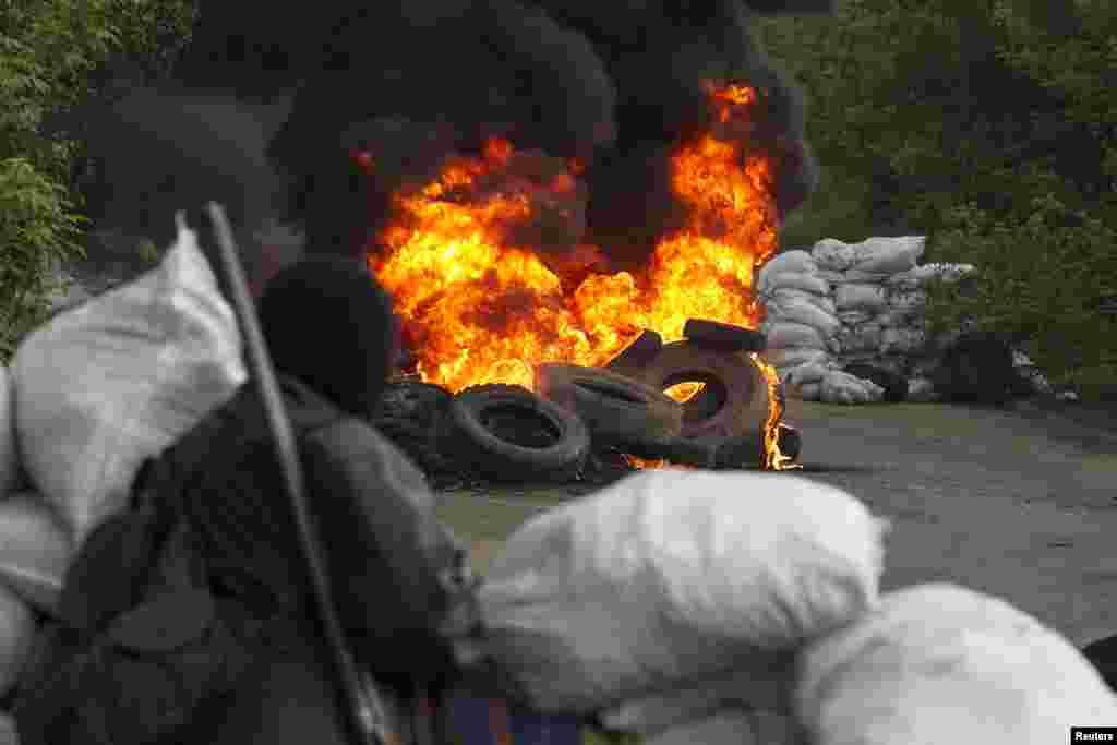 ایک چیک پوسٹ کے سامنے ٹائروں کو آگ لگی ہوئی ہے۔