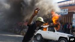 Un protestataire passe devant une voiture en feu lors d'une manifestation contre le gouvernement du président Michel Martelly à Port-au-Prince, en Haïti, le 18 janvier 2016.