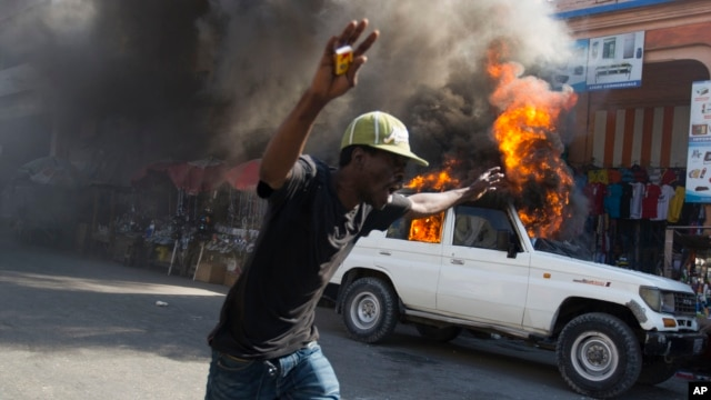 A protester runs past a burning car during a protest against President Michel Martelly's government in Port-au-Prince, Haiti, Jan. 18, 2016.
