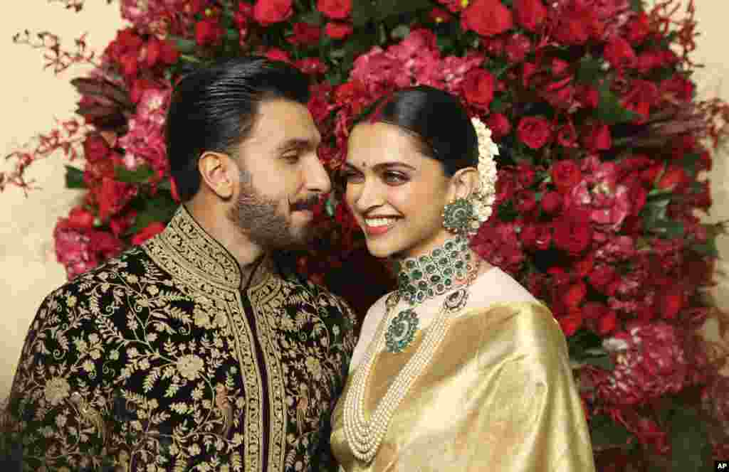 Bollywood actors Deepika Padukone, right, and Ranveer Singh pose at their wedding reception in Bangalore, India.