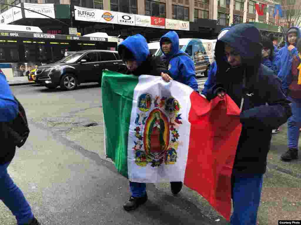 Creyentes sostienen una bandera con los colores de México, donde en el medio, se ve una imagen de la Virgen de Guadalupe, en la Ciudad de Nueva York. Foto: Celia Mendoza- VOA