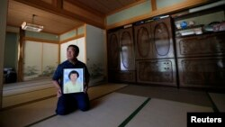 FILE - Mikio Watanabe holds a portrait of his late wife Hamako at his home at Yamakiya district in Kawamata town, Fukushima prefecture, June 23, 2014.