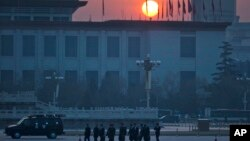 FILE - Chinese men walk on Tiananmen Square, March 5, 2015.