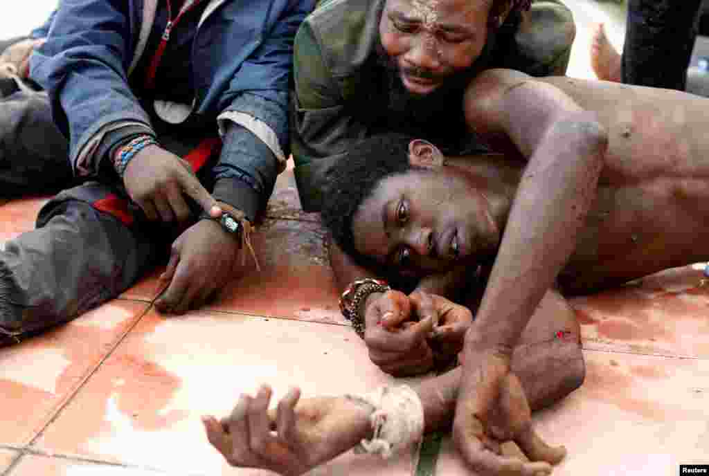 African migrants lie on the ground after crossing a border fence between Morocco and Spain's north African enclave of Ceuta, Oct. 31, 2016.