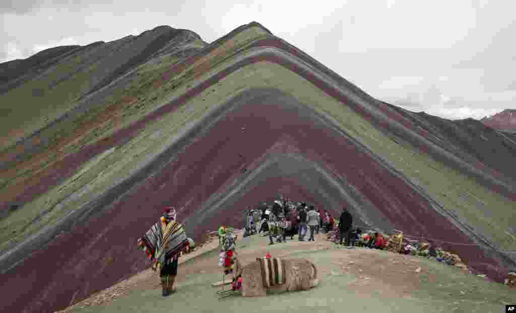 An Andean man rests with his llama while tourists take in the natural wonder of Rainbow Mountain in Pitumarca, Peru. Tourists gasp for breath as they climb for two hours to the 16,404-foot (5,000-meter) peak in the Peruvian Andes, but stunned by the magical beauty that unfurls before them.